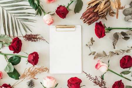 Flat lay clipboard with blank copy space for text in frame border of pink, red rose flowers, protea, tropical palm leaf, eucalyptus on beige background. Top view floral mockup. Zdjęcie Seryjne