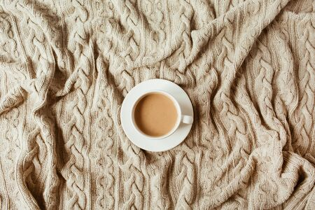 Cup of coffee with milk on beige knitted plaid blanket. Flat lay, top view still life morning breakfast concept.