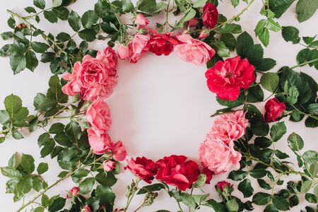 Round wreath frame border made of pink and red rose flowers and leaves. Flat lay, top view copy space mockup background. Valentines day composition.