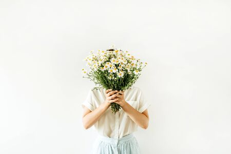 Young pretty woman hold in hands bouquet of white chamomile daisy flowers on white background. Zdjęcie Seryjne