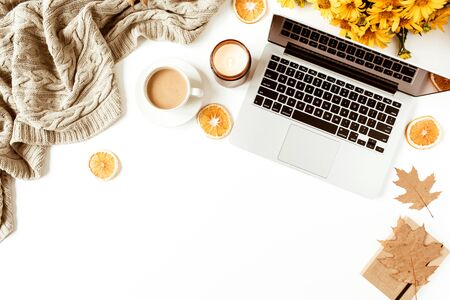 Home office table desk workspace with laptop decorated with yellow daisy flowers bouquet, coffee cup, orange slices, plaid. Flat lay, top view freelance business concept for social media, magazine. Zdjęcie Seryjne