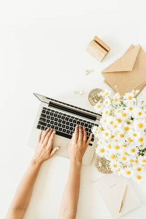 Female hands typing composition. Home office desk workspace with laptop, chamomile daisy flowers bouquet and notebook on white background. Flat lay, top view copy space mockup.
