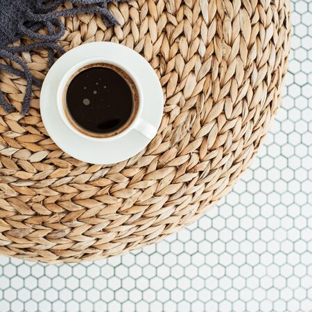 Flat lay cup of coffee, plaid blanket on rattan straw puff on white mosaic tile. Morning breakfast. Minimal modern interior design concept. Top view.