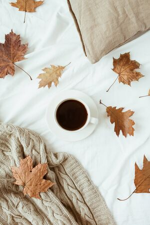 Cup of coffee with milk, dry leaves on bed with white linen, pillow, blanket. Flat lay, top view. Minimal fall autumn morning breakfast in bed composition.