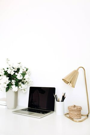 Laptop with mockup blank copy space screen on table. Office desk workspace with flowers bouquet, table lamp. Minimal freelance co-working concept.