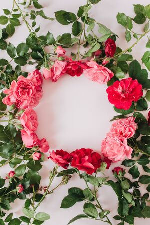 Round wreath frame border made of pink and red rose flowers and leaves. Flat lay, top view copy space mockup background. Zdjęcie Seryjne