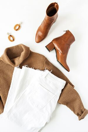 Flat lay fashion collage with women modern clothes and accessories on white background. Brown turtleneck pullover, shoes, jeans, earrings. Lifestyle, beauty concept for blog, social media, magazine. Banque d'images - 135492957