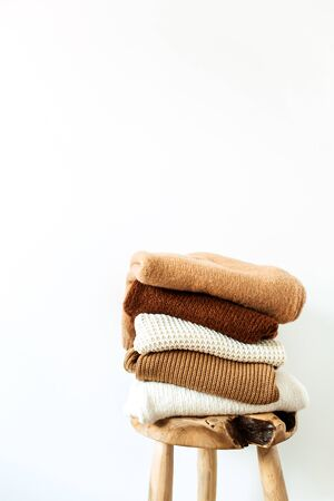Women fashion composition. Warm winter female woolen knitted sweaters, pullovers stack on wooden stool at white background. Modern clothes concept for magazine, blog, social media. Reklamní fotografie