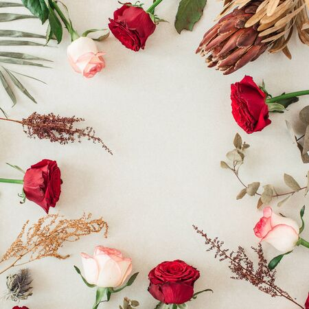 Round frame border of pink, red rose flowers, protea, tropical palm leaf, eucalyptus on beige background. Mockup blank copy space. Flat lay, top view floral composition.