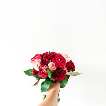 Female hand hold pink and red rose flowers bouquet isolated on white background. Holiday, Valentines day present.
