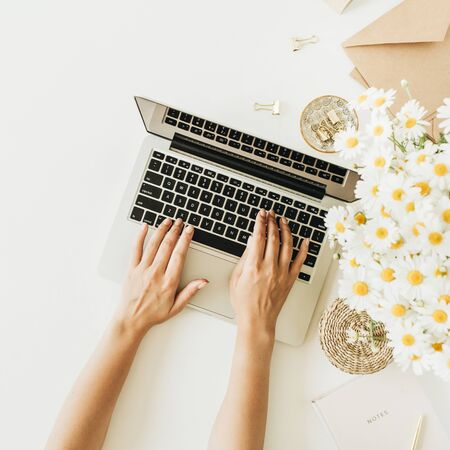 Female hands typing composition. Home office desk workspace with laptop, chamomile daisy flowers bouquet and notebook on white background. Flat lay, top view concept with copy space mockup.
