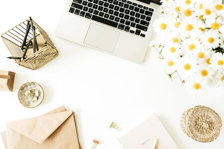 Home office desk workspace with laptop, chamomile daisy flowers bouquet and notebook on white background. Flat lay, top view minimal freelancer work concept with copy space mockup.