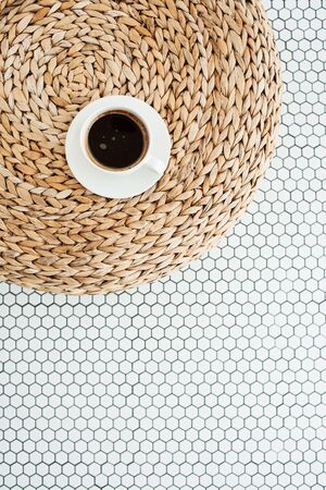 Flat lay cup of coffee on rattan straw puff on white mosaic tile. Morning breakfast. Minimal modern interior design concept. Top view.