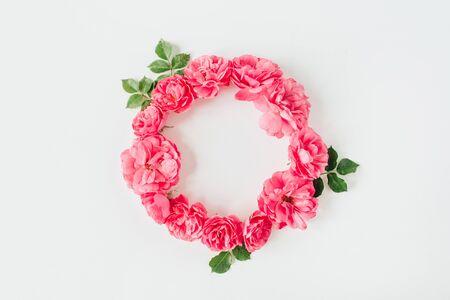 框架边框由粉红色的玫瑰花和叶子制成。平的位置,顶视图拷贝空间样机背景。