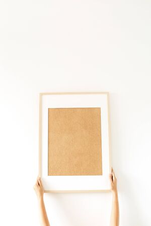 Blank photo frame with empty mockup copy space in womens hands. Minimal watercolor art concept.