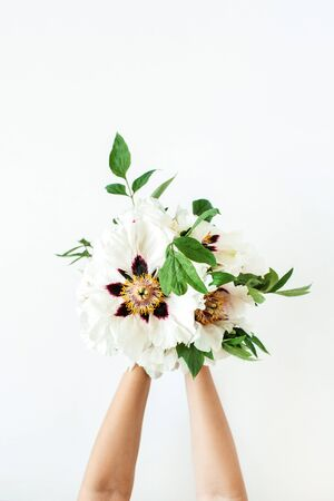 Woman hands holding white peonies flowers on white background. Flat lay, top view.