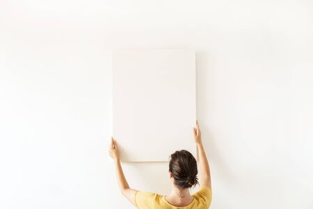 Blank canvas with empty mockup copy space in female hands. Minimal art concept.