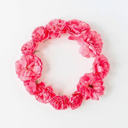 圆的花圈框架边界由桃红色玫瑰花朵制成。平的位置,顶视图拷贝空间样机背景。