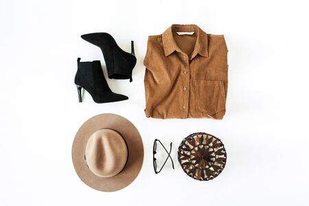 Flat lay fashion collage with women modern clothes and accessories on white background. Brown shirt, shoes, glasses, hat, purse bag. Lifestyle, beauty concept for blog, social media, magazine.