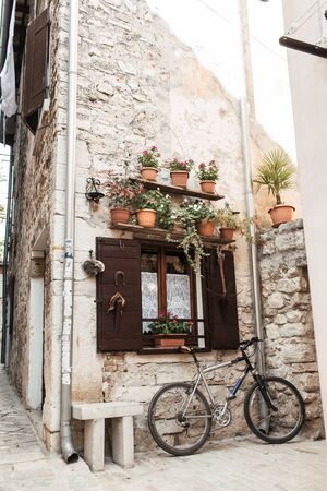 2019, Europe, Croatia, Rovinj. Architecture of old town of Rovinj. Stone building with bicycle, terracotta pots with plants and little bench. Travel, adventure concept. City background.