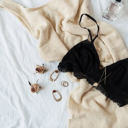 Fashion concept. Women's clothes and accessories. Lace bra, dress, earrings, sunglasses, perfume in bed with white linen. Archivio Fotografico