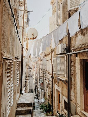 Narrow street of Dubrovnik, Croatia, Europe 2019. Travel concept. Old buildings with clotheslines across the street with white linen.