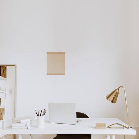Modern minimal interior design concept. Bright Scandinavian home office desk table workspace with laptop, lamp, books. Business study cabinet. Girl boss studio concept.