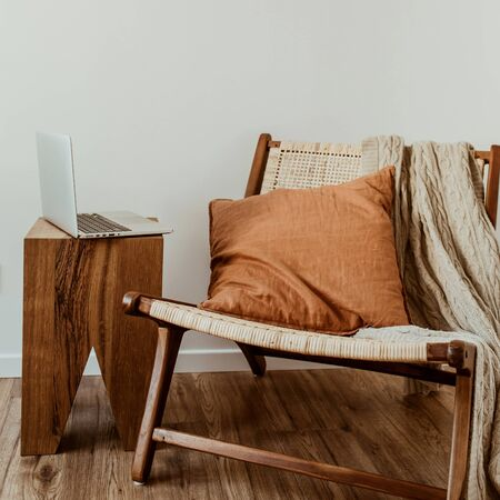 Modern interior design concept. Stylish rattan wooden chair, knitted plaid, ginger pillow. Cozy comfortable home office workspace with laptop.