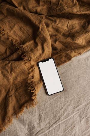 Blank screen mobile phone on brown, beige blanket. Flat lay, top view. Copy space mockup template. 版權商用圖片