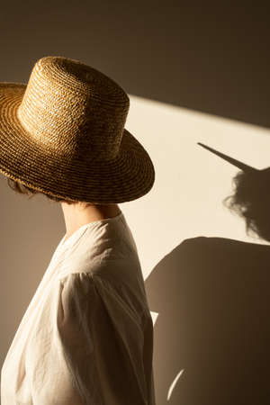 Young pretty woman in straw hat and white dress / sundress against the wall. Sunlight shadow on the wall. Minimal fashion design concept.