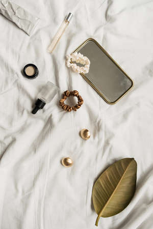 Fashion female accessories and cosmetics on white linen. Flat lay, top view. Minimalist lifestyle composition.