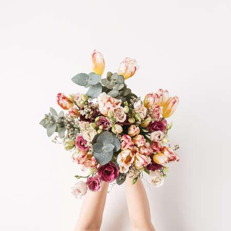 Female hand holding tulip, eucalyptus flowers bouquet against white wall. Holiday celebration festive floral concept 版權商用圖片