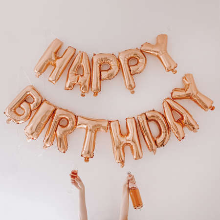 Happy Birthday! Rose gold sparkling balloons on white background. Holiday celebration party anniversary decoration composition. Female hands hold rose champagne bottle and glass 版權商用圖片