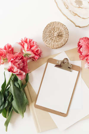 Blank paper sheet clipboard tablet pad with mock up copy space. Beautiful home office table desk workspace with fresh pink peony tulip flowers, marble tray, rattan casket, albums. Flat lay, top view