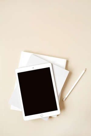 Tablet pad with blank touch screen on neutral beige background. Flat lay, top view empty mockup with copy space. Freelancer, blogger, web designer minimalist home office workspace