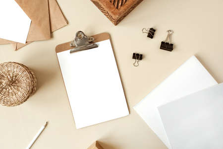Clipboard tablet pad with blank paper sheet on beige table. Artist home office desk workspace with wooden casket, pencil, envelopes and stationery. Flat lay, top view mockup with empty copy space 版權商用圖片