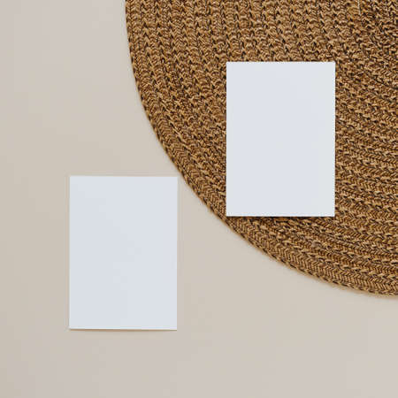 Blank paper cards with mockup copy space and wicker napkin on beige background. Minimal business brand template. Flat lay, top view. 版權商用圖片