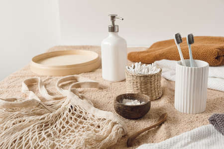 Beauty health care composition with ear sticks in rattan casket, towel, powder, toothbrushes, liquid soap on beige towel. Female beauty treatment routine concept