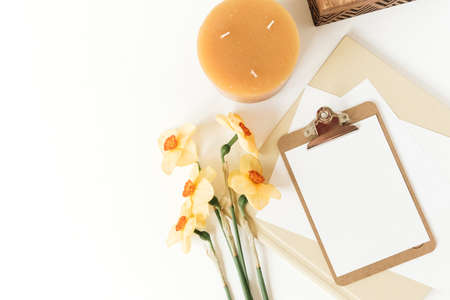 Blank clipboard tablet pad with mock up copy space and narcissus flowers. Flat lay, top view