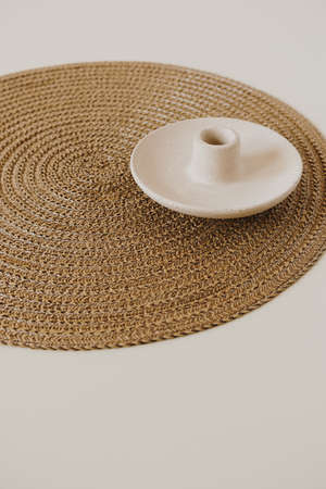 Candlestick and wicker napkin on neutral beige and white background. Minimal modern interior decoration concept.