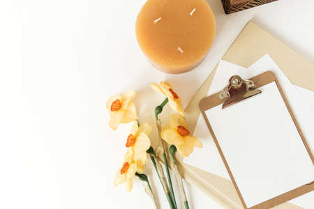 Blank paper sheet clipboard tablet pad with mock up copy space. Beautiful home office table desk workspace with fresh narcissus flowers, wooden casket, candle, albums. Flat lay, top view art concept