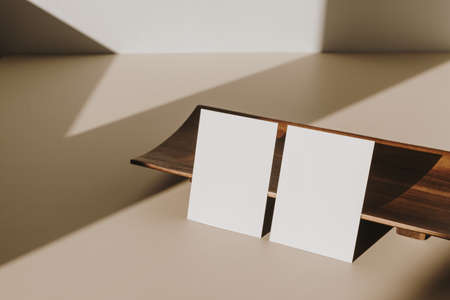 Blank paper sheet cards with mockup copy space and wooden tray with sunlight shadow on beige table. Minimal business brand template