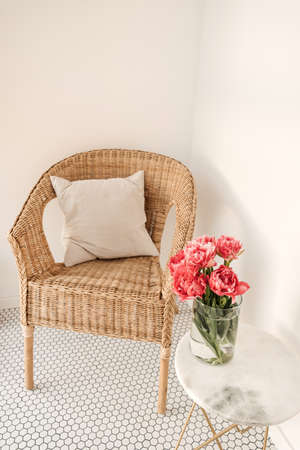 Cozy comfortable home rest space with rattan chair, white wall, mosaic tile, marble table with beautiful peony flower bouquet. Modern interior design concept