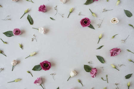 Round frame made of roses flowers on gray background. Flat lay, top view festive holiday celebration. Copy space mockup