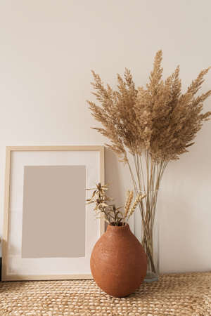 Blank photo frame, fluffy reeds bouquet in vase, rye in clay pot at white wall. Copy space mockup template. Minimalist interior design concept.