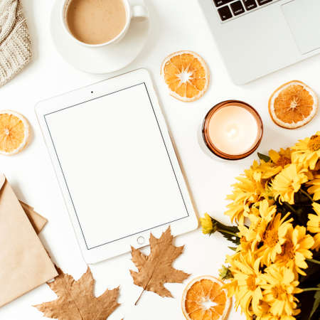 Home office table desk workspace with blank screen tablet with copy space. Yellow daisy flowers bouquet, orange slices. Flat lay, top view freelance business concept for social media, magazine.