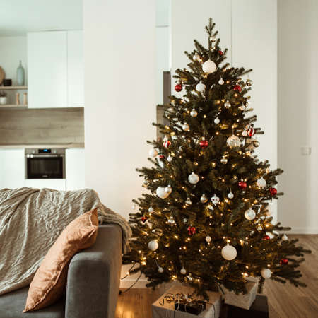 Minimalist modern home interior design concept. Comfortable cozy living room decorated with Christmas tree with gifts, sofa, plaid. Christmas / New Year celebration decorations.