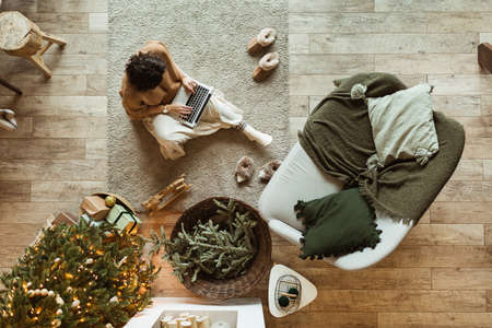 Young beautiful woman sitting on carpet and work on laptop in cozy comfortable living room decorated for Christmas / New Year holidays celebration. Christmas tree, sofa, blanket, decorations. Top view