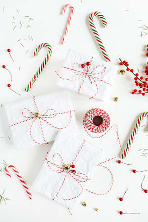Christmas gift boxes with festive candies, branch with red berries, reel of christmas rope and fir needles on white table. Christmas, new year composition. Flat lay, top view. Zdjęcie Seryjne