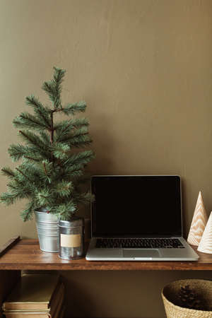 Blank screen laptop with mockup copy space on wooden stand decorated with fir tree, books, straw basket. Minimalist home office desk workspace. Zdjęcie Seryjne